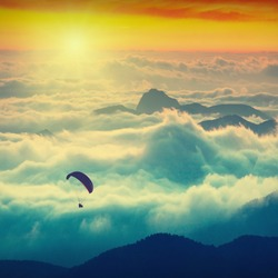 Paraglide silhouette over mountain peaks. Sunrise in a high mountains foggy valley of Crimea, Ukraine