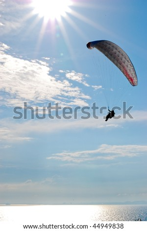 Paraglider against sun on blue sky vertical