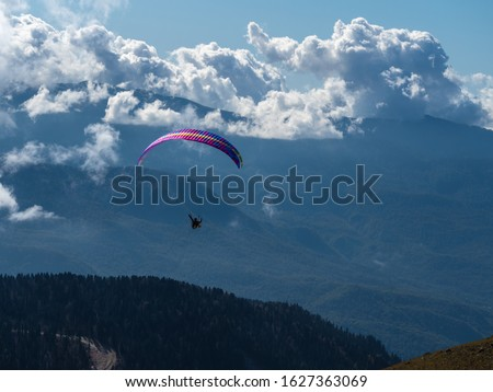 Paraglider flies above the clouds over the mountains and over the forest