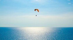 Paraglider flies over the Costa Del Sol past the bright sun in Spain.