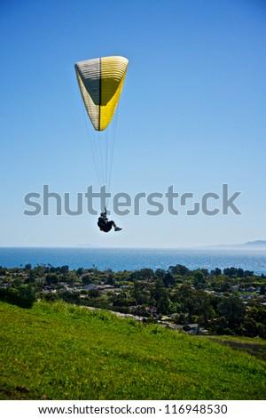 Paraglider flies through the air above the city of Santa Barbara, California.