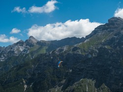 Paraglider fly over limestone mountain peaks. Kiting in blue and orange kite in Stubai valley Tirol Alps, Austria, Summer blue sky, white clouds