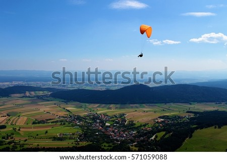 paraglider flying above a beautiful mountain landscape and fields/leisure time sport/feeling fee in the sky