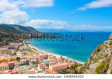 Paraglider flying above the amazing landscape of coastal city Cefalu in beautiful Sicily. Paragliding is a popular extreme sport. Cefalu is one of the major tourist destinations in Italy.
