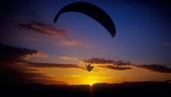 Paraglider flying against a sunset. Crimea, Ukraine.