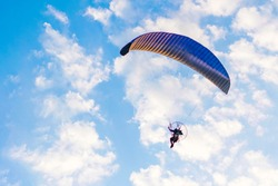 Paraglider flying against the blue sky with clouds, outdoor activities, extreme sports, extreme sport, paraglider flying in the sun