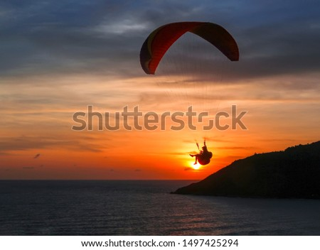 Paraglider flying at sunset over the sea. Beautiful sunset landscape with the Andaman Sea of the Indian Ocean and paraglider flying against the sky. Aerial shot of the evening sun reflected in water