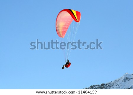 Paraglider flying high over the mountains in winter