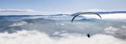 Paraglider flying high up in the air above the clouds and mountains on a sunny peaceful day