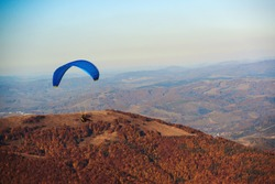 Paraglider flying in autumn mouintain. Paragliding concept. Beauty nature carpathian mountains landscape. Autumn vacation, travel. Paraglider flying over mountains in autumn. Extreme sport, lifestyle.