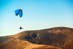 Paraglider flying in mountains. Paragliding concept. Beautiful nature carpathian mountains landscape. Autumn vacation and travel. Paraglider flying over mountains in autumn. Extreme sport, lifestyle.