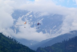 Paraglider flying in the Kullu valley in the village . District Manali, Himachal Pradesh, India.