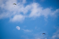 Paraglider flying in the sky with moon
