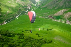 Paraglider flying near high mountains. Chegem. Russia.