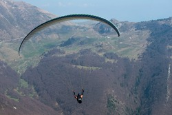 Paraglider flying on gorge over Garda lake. Adrenalin sport activity. Dangerous hobby.