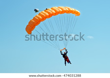 paraglider flying on orange...