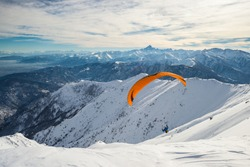 Paraglider flying on snowy slope with bright orange kite. Stunning background of the italian Alps in winter season. Shot taken in backlight, unrecognizable person.