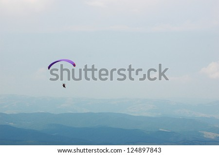 Paraglider flying over a blue sky. Risk, sport, adventure, flight, high. recreation, outdoor, active, freedom, extreme,  leisure, activity, excitement, hobby