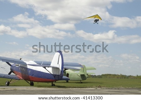 Paraglider flying over airplanes at little sport airport