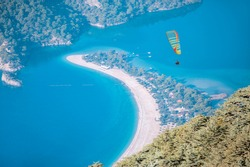 Paraglider flying over Babadag on the background of oludeniz beach.