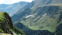 Paraglider flying over mountains during summer day - Georgia, kazbegi