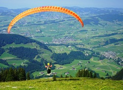 Paraglider flying over mountains in Swiss Alps.