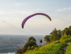 Paraglider flying over the big city.