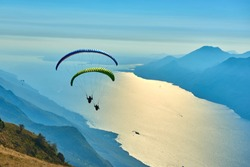 Paraglider flying over the Garda Lake,Panorama of the gorgeous Garda lake surrounded by mountains, Malcesine,Italy