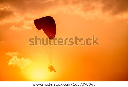 Paraglider flying with para motor on sunset background