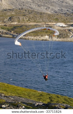 Paraglider hanging over the ocean. There is a mountain face in the background.