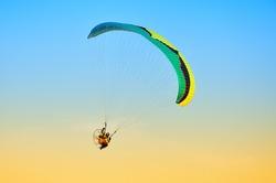 paraglider in flight in blue sky