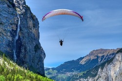 Paraglider in the blue sky. The sportsman flying on a paraglider. Leisure sports activity in holiday