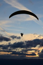 Paraglider in the cloudy sunset sky