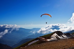 Paraglider in the sky above the mountains in the clouds picturesque view spring summer nature russia red glade extreme