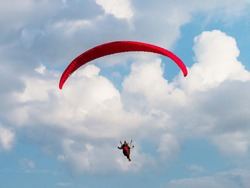 Paraglider is flying in the blue sky.