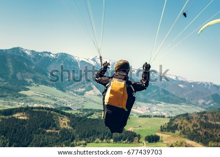 Paraglider is on the paraplane strops - soaring flight moment #677439703