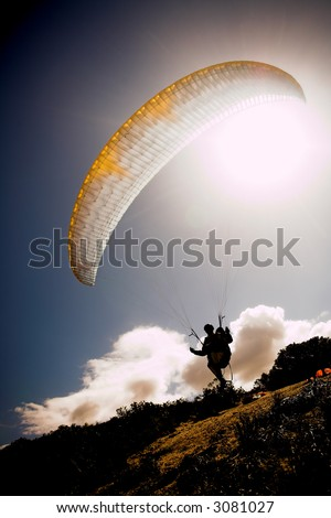 Paraglider launching from the ridge with a yellow and white canopy and the sun from behind. The paraglider is a silhouette. The paraglider is sharp, with slight movement on the wing