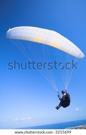 Paraglider launching from the ridge with a yellow and white canopy. The shot is taken right after takeoff. The canopy wingtip is sharp, with slight movement on the closer wing and the pilot