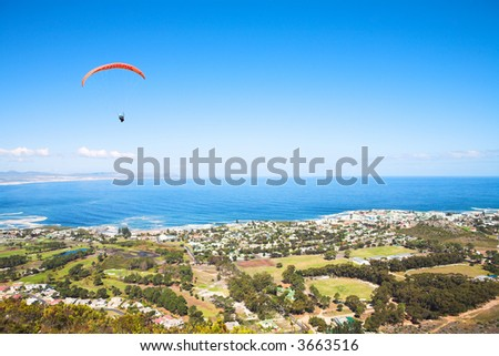 Paraglider launching from the ridge with an orange canopy against a blue sky. The town of Hermanus (Western Cape, South Africa) in the bottom of the screen - Editorial use only
