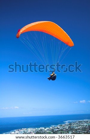 Paraglider launching from the ridge with an orange canopy against a blue sky. The town of Hermanus (Western Cape, South Africa) in the bottom of the image