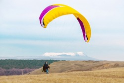 Paraglider preparing for launch, takeoff and start. Man with paraplane and equipment for flying. Paragliding. Extreme sport.