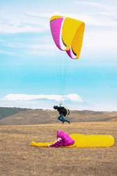 Paraglider preparing for launch, takeoff and start. Man with paraplane equipment for flying. Paragliding. Extreme sport.