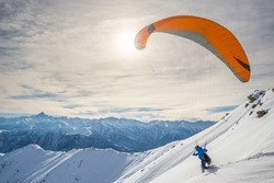 Paraglider running on snowy slope for take off with bright orange kite. Stunning background of the italian Alps in winter season. Shot taken in backlight, unrecognizable person.