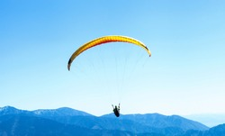 Paraglider soaring in the sky over the blue mountains