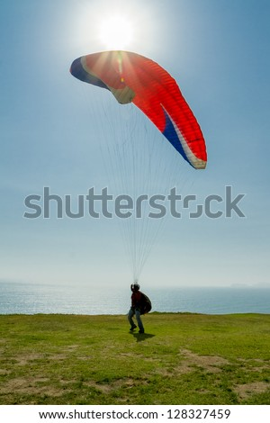 Paraglider taking off from a cliff