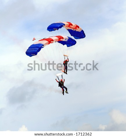 Paragliders descending in a military skydiving parachute demonstration