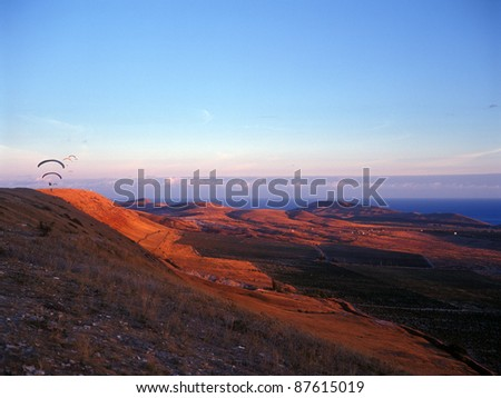 Paragliders flying against a sunset. Crimea, Ukraine.