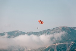 Paragliders flying against the sky and mountains with white clouds. Red and white parachute on a clear blue sunny day with clouds.