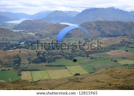 Paragliders in flight above the Queenstown countryside. South Island. New Zealand