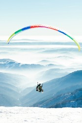 Paragliders launched into air at the peak of a mountain